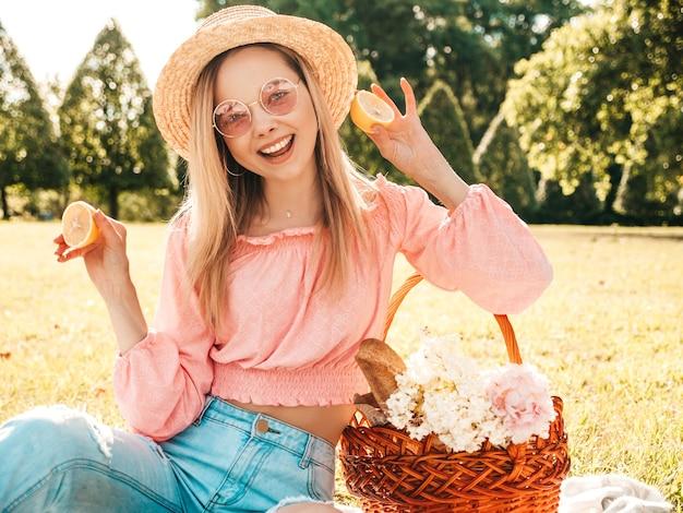 Mujer joven hermosa hipster en jeans de moda de verano, camiseta rosa y sombrero. mujer haciendo picnic afuera.
