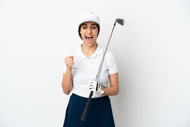 Mujer joven hermosa del jugador del golfista aislada en el fondo blanco que celebra una victoria en la posición ganadora