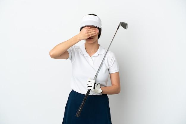 Mujer joven hermosa del jugador del golfista aislada en la pared blanca que cubre los ojos con las manos
