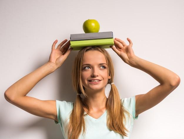 Mujer joven hermosa con libros y manzana en su cabeza.