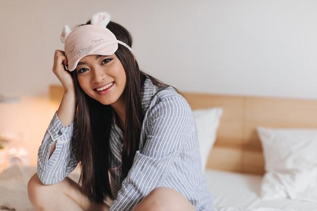 Mujer joven en hermosa máscara para dormir con sonrisa mira al frente