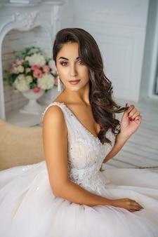 Mujer joven hermosa en novia feliz hermosa del maquillaje y del peinado del vestido de boda.