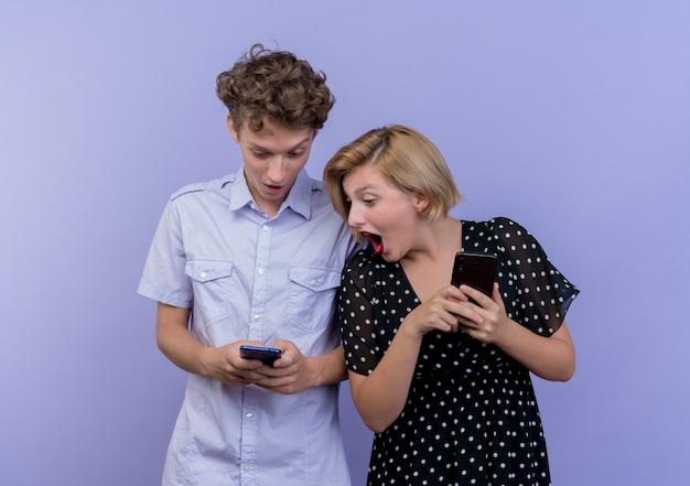 Mujer joven hermosa pareja espiando mirando el teléfono celular de su novio sobre azul