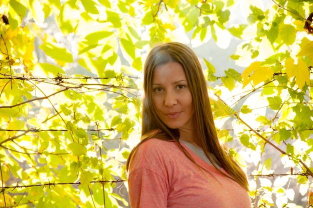 Mujer joven y hermosa en el parque de otoño brillante y colorido