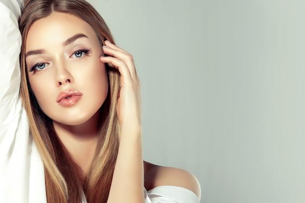 Una mujer joven y hermosa con un peinado largo y recto y un maquillaje elegante está tocando su propio rostro.