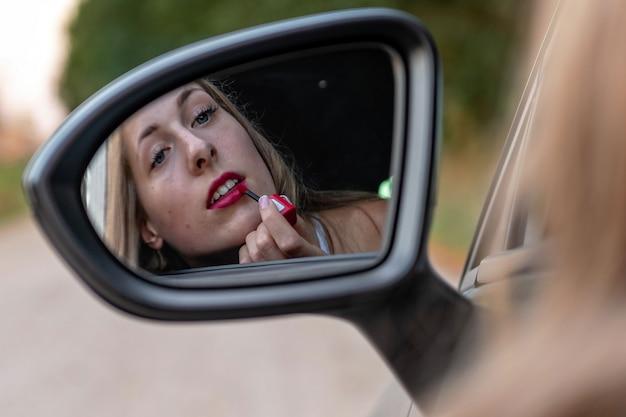 Una mujer joven y hermosa con el pelo largo se mira en el espejo retrovisor del coche y se pinta los labios.