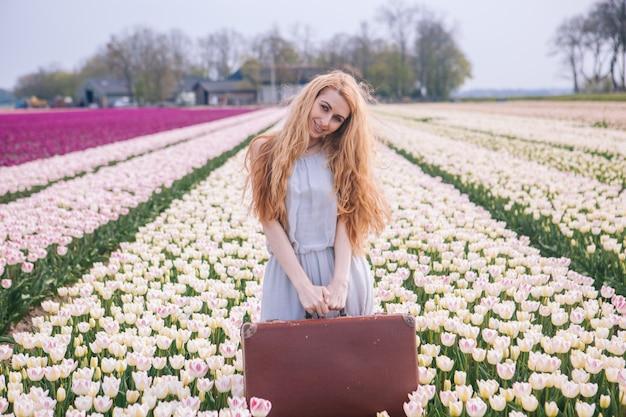 Mujer joven hermosa con el pelo rojo largo que lleva en el vestido blanco que se coloca con la maleta vieja del vintage en campo colorido del tulipán.