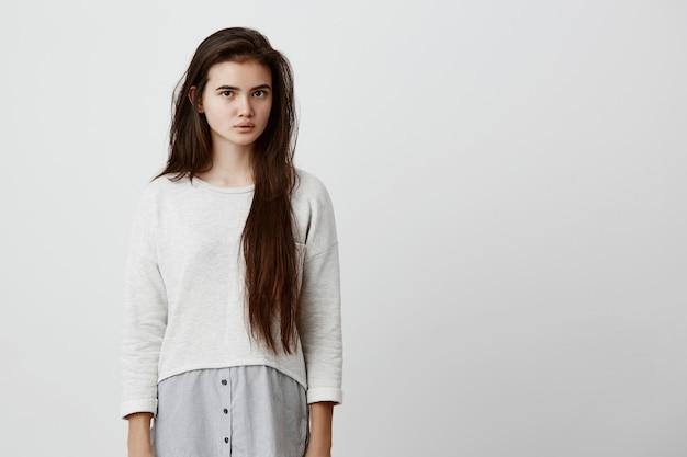 Mujer joven hermosa pensativa con cabello largo y liso oscuro en ropa casual mirando pensativa y tranquila