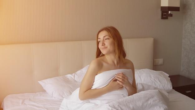 Mujer joven hermosa positiva se despierta en la cama grande y mira por la ventana, la luz del sol