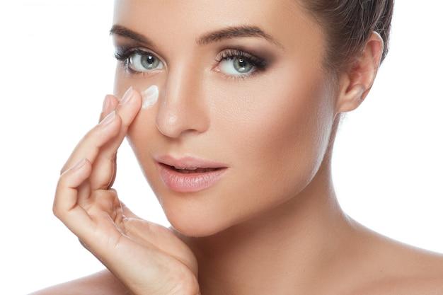 Mujer joven y hermosa que aplica la crema hidratante en su cara