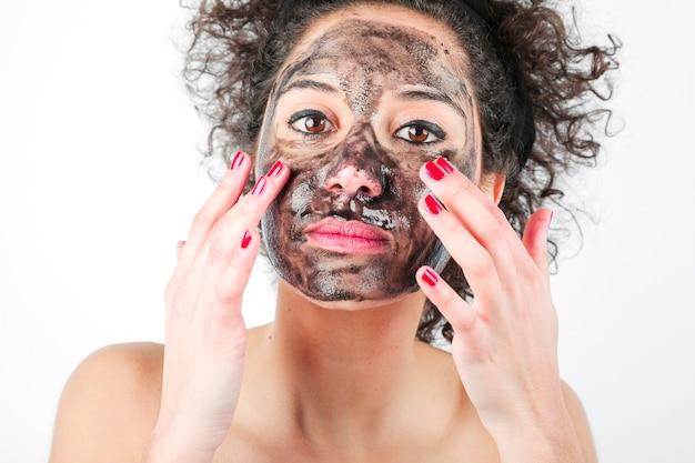 Mujer joven hermosa que aplica la mascarilla negra con sus dedos contra el fondo blanco