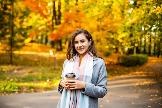 Mujer joven hermosa que bebe el café para llevar en parque en otoño.