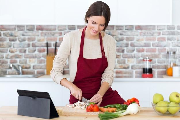 Mujer joven hermosa que cocina y que usa la tableta digital en la cocina.