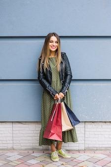 Mujer joven hermosa que se coloca delante de la pared que sostiene bolsos de compras coloridos