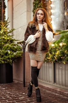 Mujer joven hermosa que se coloca en el invierno en la calle cerca de la decoración festiva de la navidad de la ventana en las calles