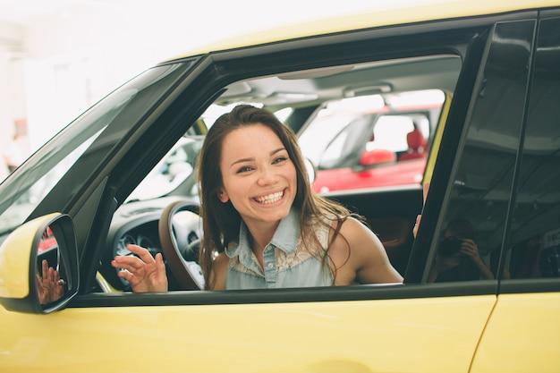 Mujer joven hermosa que compra un coche en el concesionario. modelo femenino sentado se sienta en el interior del automóvil