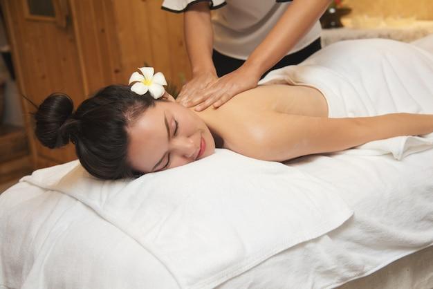 Mujer joven hermosa que consigue el salón del masaje del balneario y la flor blanca en su oído.