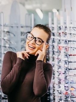 Mujer joven hermosa que elige el nuevo par de gafas en tienda de los ópticos.