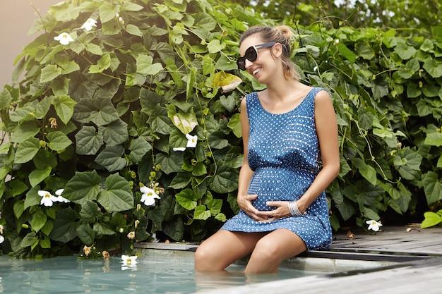 Mujer joven hermosa que espera al niño que descansa en la piscina