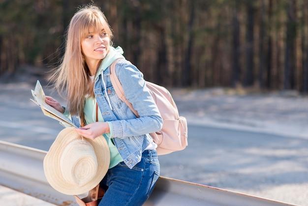 Mujer joven hermosa que se inclina en el mapa y el sombrero de la tenencia de la verja que miran lejos