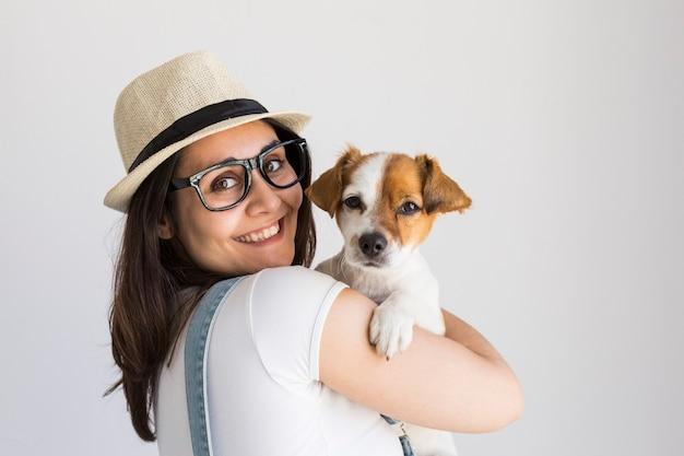 Mujer joven hermosa que juega con su pequeño perro lindo en casa.