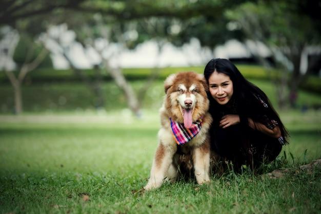 Mujer joven hermosa que juega con su pequeño perro en un parque al aire libre. retrato de estilo de vida