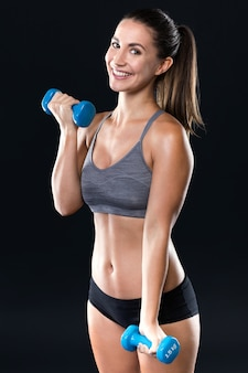 Mujer joven hermosa que levanta pesas de gimnasia sobre fondo negro.