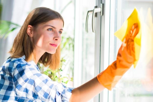 La mujer joven hermosa que lleva guantes amarillos limpia el vidrio de la ventana con la servilleta amarilla