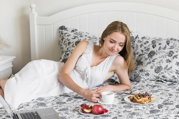 Mujer joven hermosa que miente en la cama que mira el desayuno