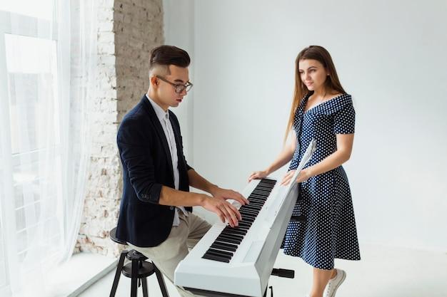 Mujer joven hermosa que mira al hombre que toca el piano en casa