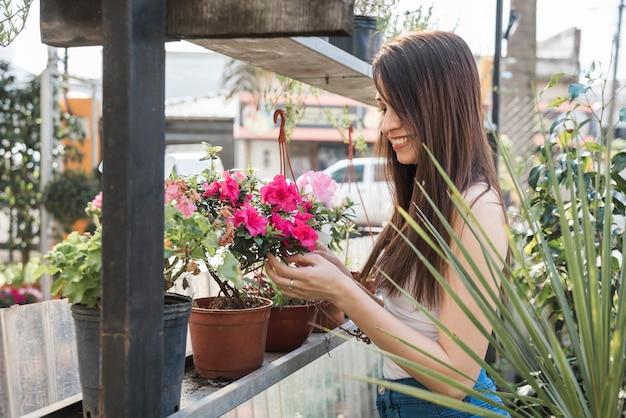 Mujer joven hermosa que mira la flor rosada hermosa