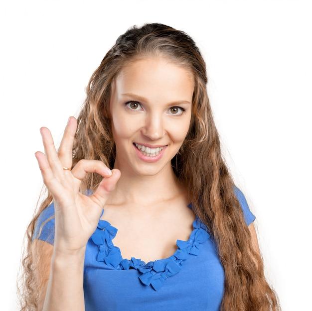 Mujer joven hermosa que muestra la muestra aceptable
