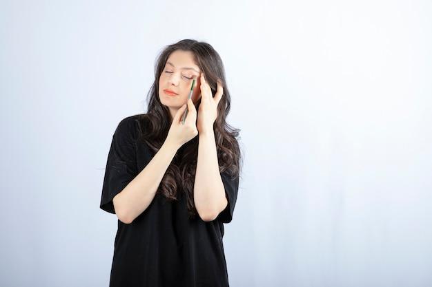 Mujer joven hermosa que pone sombra con el cepillo cosmético sobre la pared blanca.
