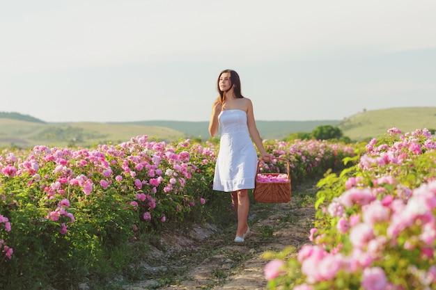 Mujer joven hermosa que presenta cerca de rosas en un jardín.