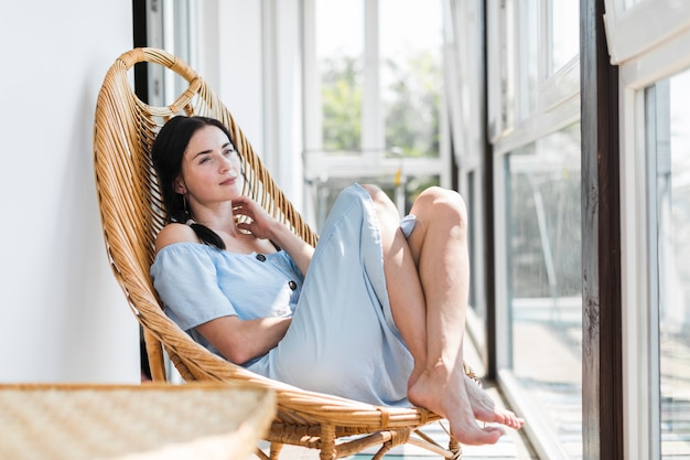 Mujer joven hermosa que se relaja en silla de madera en el patio