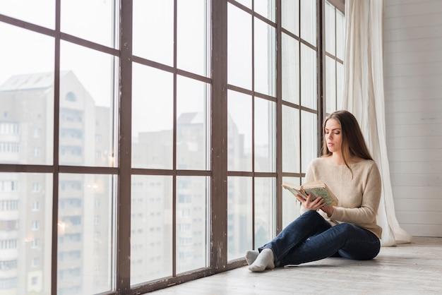 Mujer joven hermosa que se sienta cerca del libro de lectura de la ventana de cristal