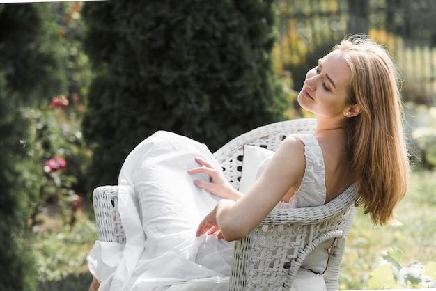Mujer joven hermosa que se sienta en la silla al aire libre blanca en el jardín doméstico