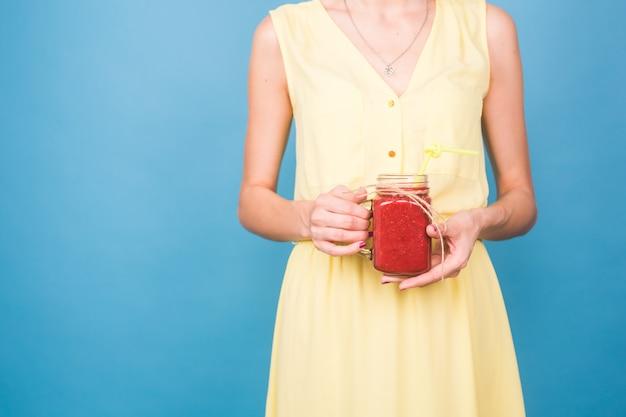 Mujer joven hermosa que sostiene el batido de fresa en azul. concepto de bebidas orgánicas saludables. personas a dieta.