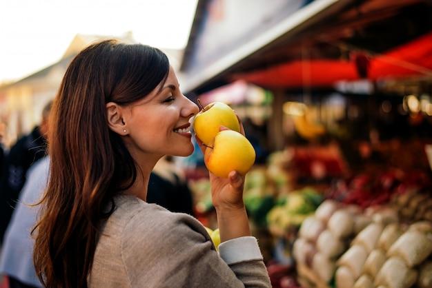 Mujer joven hermosa que sostiene la manzana y que lo huele