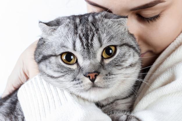 Mujer joven hermosa que sostiene el pequeño gatito en manos y que se une a él