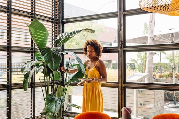 Mujer joven hermosa que sostiene el plato que se coloca cerca de la planta verde