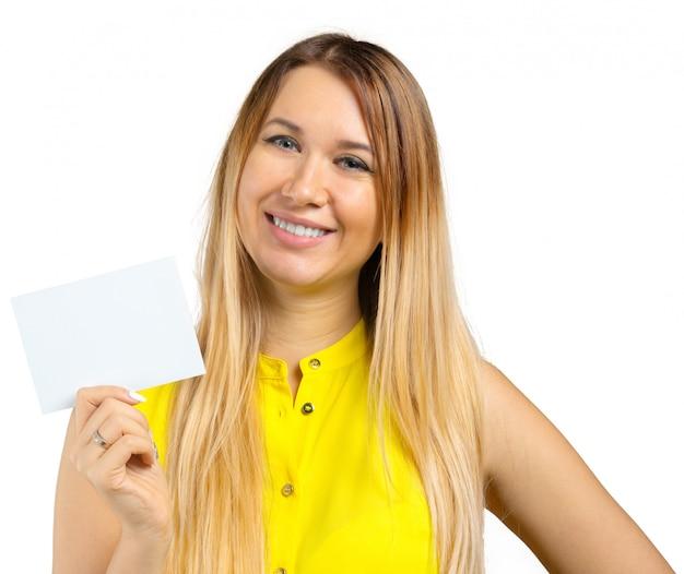 Mujer joven hermosa que sostiene la tarjeta en blanco. aislado en blanco