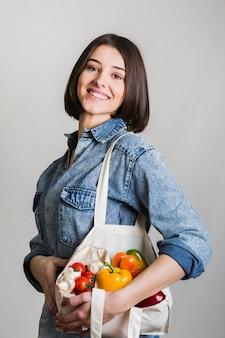Mujer joven hermosa que sostiene verduras orgánicas
