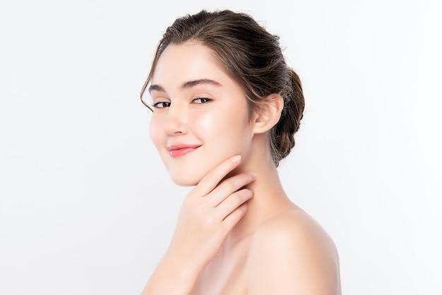 Mujer joven hermosa que toca su cara limpia con la piel sana fresca, aislada, cosméticos de la belleza y concepto del tratamiento facial.
