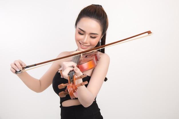 Mujer joven hermosa que toca el violín sobre el fondo blanco