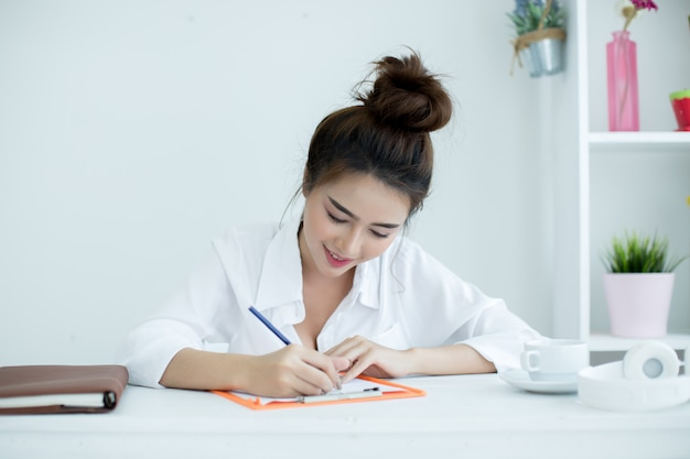 Mujer joven hermosa que trabaja en su computadora portátil en su sitio.