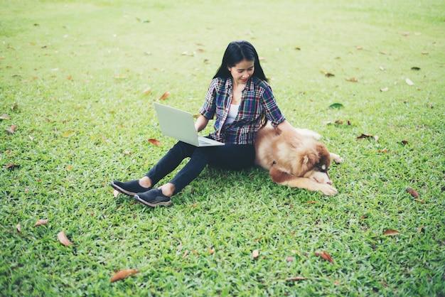 Mujer joven hermosa que usa la computadora portátil con su pequeño perro en un parque al aire libre. estilo de vida.
