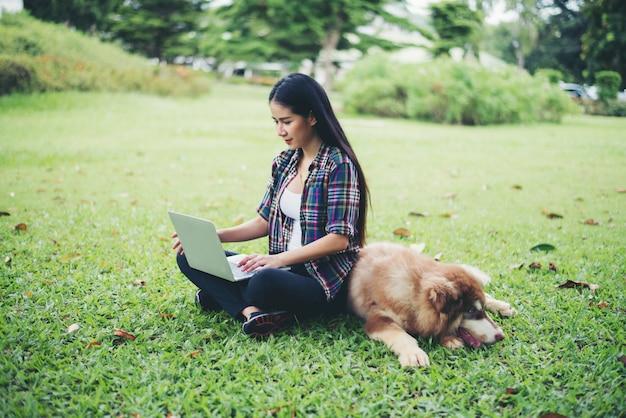 Mujer joven hermosa que usa la computadora portátil con su pequeño perro en un parque al aire libre. retrato de estilo de vida