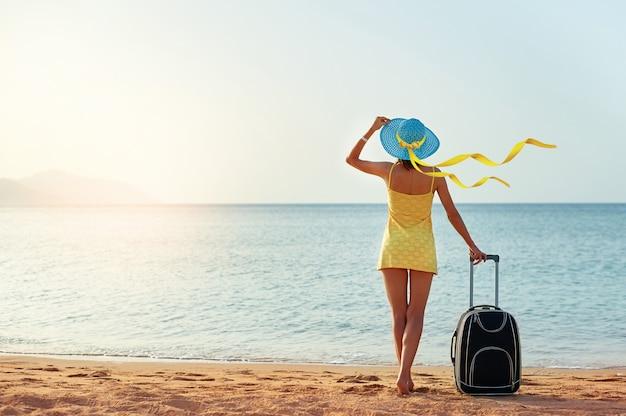 Mujer joven hermosa con un sombrero que se coloca con la maleta en el fondo maravilloso del mar