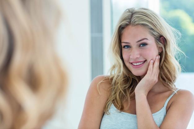 Mujer joven hermosa sonriente que se mira en el espejo del cuarto de baño en casa